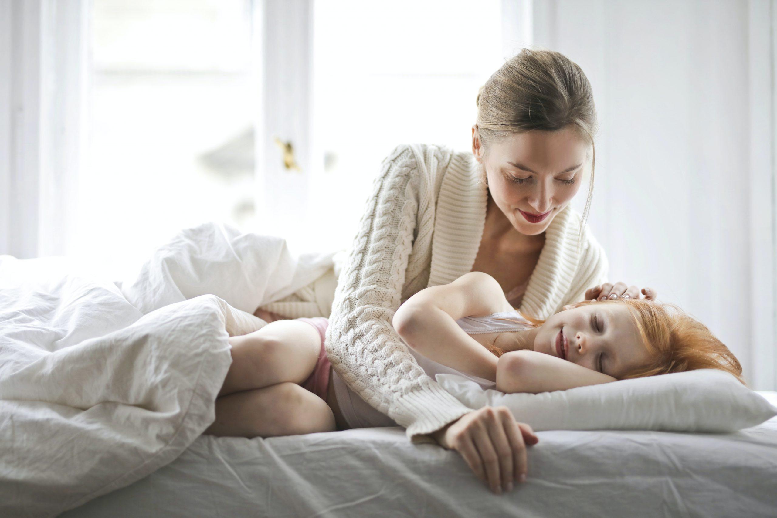 kind kruipt in bed samen slapen ouder kind